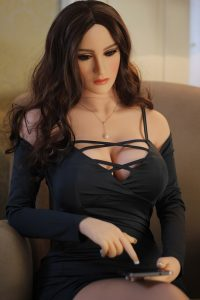 Haley is a MILF sex doll by ovdoll.com She is wearing a black lace top and is depicted using a smartphone and wearing long brown hair.