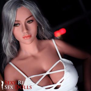 An unnamed sex doll that is caucasian and has dyed grey hair but looks awesome with it. She wears a white lace top which are barely covering her breasts.